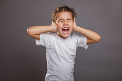 Teen girl screams closes ears gray background Royalty Free Stock Photos