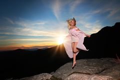 Teen girl dancing on a rock overlook in the mountains stock image