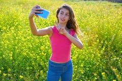 Teen girl selfie video photo spring meadow. Teen girl serfie video photo in spring meadow gesturing stock photo