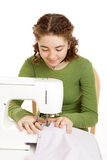 Teen Girl Sewing. Pretty teen girl using a sewing machine. Isolated on white stock photography