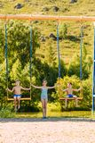 Teen girl shakes her children on the big swings in the summer stock images