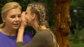 Teen girl sharing secret, whispering to mother, first kiss revelation, trust. Stock footage stock video footage