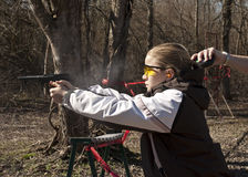Teen girl shooting pistol with coach's hand timing royalty free stock image