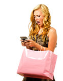 Teen girl with shopping bag texting. Portrait of teen girl with pink shopping bag texting with shocked or surprised expression isolated on white Stock Images