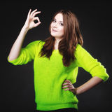 Teen girl showing ok sign hand gesture on black Stock Photography