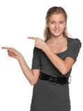 Teen girl shows her fingers to the side Royalty Free Stock Images