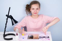 Teen girl shows her hands good and bad, on the table lie glasses and lenses to improve vision royalty free stock photography