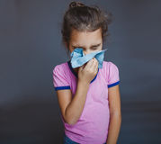 Teen girl is sick sneezes handkerchief on gray Stock Photography