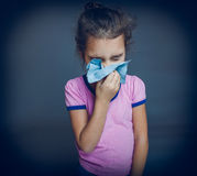 Teen girl is sick sneezes handkerchief on a gray Royalty Free Stock Images