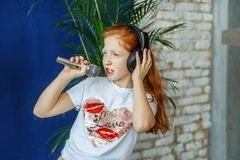 A teen girl sing a song in a microphone.  is childhood, lifestyl. A teen girl sing a song in a microphone. The concept is childhood, lifestyle, music, singing Stock Photos
