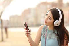 Teen girl singing and listening music from a smart phone. Funny teen girl singing and listening music from a smart phone with headphones in an urban park Stock Photo