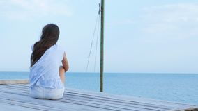 Teen girl sits alone on a wooden bridge at the sea and looks sad at the sea stock video footage