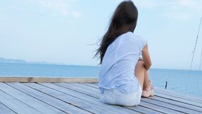 Teen girl sits alone on a wooden bridge at the sea and looks sad at the sea stock footage