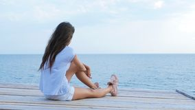 Teen girl sits alone on a wooden bridge at the sea and looks sad at the sea stock video
