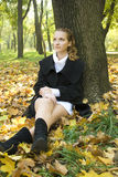 Teen girl sits under the tree in autumn park Royalty Free Stock Photography