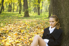 Teen girl sits under the tree leaves in park. Teen girl sits under the tree among gold leaves in autumn park Royalty Free Stock Photo