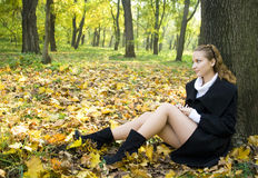 Teen girl sits under the tree leaves in park. Teen girl sits under the tree among gold leaves in autumn park Royalty Free Stock Photos
