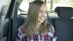Teen girl on back seat in car. Teen girl sitting in the back seat of car. Happy child enjoying leisure in automobile during sunny day road trip stock video footage