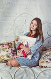 Teen girl sitting on a bed Royalty Free Stock Image