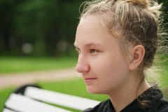 Teen girl sitting on bench in park Stock Images