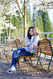 Teen girl sitting on bench under cherry tree Stock Images