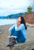 Teen girl sitting on boulder along lake shore praying Royalty Free Stock Image