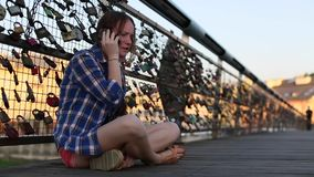 Teen girl sitting on the bridge of lovers with snaps, talking on a cell phone. stock video footage