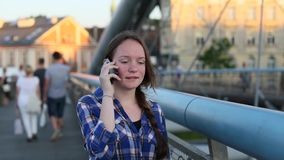Teen girl sitting on the bridge of lovers with snaps, talking on a cell phone. stock footage