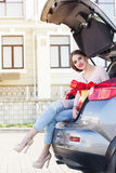 Teen girl is sitting in car trunk with red tulips Royalty Free Stock Photography