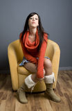 Teen girl sitting in chair. Full length view of teenage girl sitting in yellow armchair Royalty Free Stock Photo