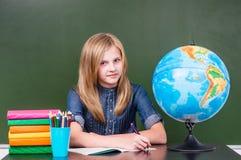 Teen girl sitting in classroom near empty green chalkboard