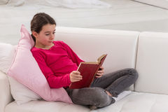 Teen girl sitting on couch at home and reading a Stock Photography