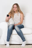 Teen girl sitting on the couch and looking at the phone Stock Image