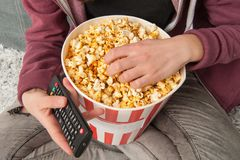 Teen girl sitting on couch with TV remote and eating popcorn stock image