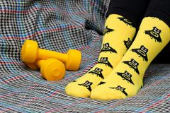 Teen girl sitting on couch. Yellow socks with black Batman pattern. Dumbbells. Side view stock photos
