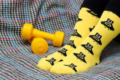 Teen girl sitting on couch. Yellow socks with black Batman pattern. Dumbbells. Side view royalty free stock photos