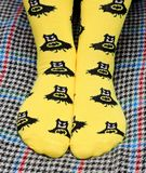 Teen girl sitting on couch. Yellow socks with black Batman pattern. Side view stock photography