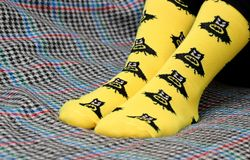 Teen girl sitting on couch. Yellow socks with black Batman pattern. Side view royalty free stock photography