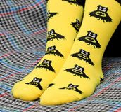 Teen girl sitting on couch. Yellow socks with black Batman pattern. Side view royalty free stock photo