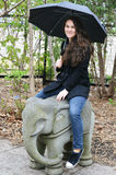Teen Girl Sitting on Elephant Statue Stock Photography