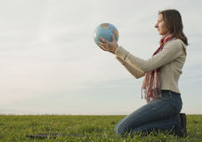 Teen girl sitting with a globe. On the grass Royalty Free Stock Photo