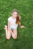 Teen girl sitting on the grass in the park. She looks into. Cute teen girl sitting on the grass in the park. She looks into the camera Stock Images