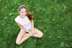 teen girl sitting on the grass in the park. She looks into Stock Images