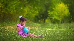 Teen girl sitting on  green  grass playing stock video footage