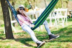 Teen girl sitting in hammock on garden party and eating cake stock photo