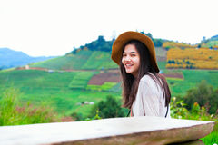 Teen girl sitting on hillside of Thailand Stock Photos