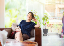 Teen girl sitting in hotel lobby waiting and laughing Royalty Free Stock Photos