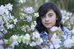 Teen girl sitting in a meadow of wildflowers Royalty Free Stock Photos