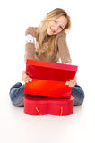 Teen girl sitting near the gift boxes isolated Stock Photos