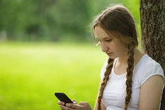 Teen girl sitting near tree with mobile phone Stock Image